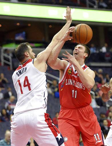 Washington Wizards forward Jason Smith (14) fouls Guangzhou Long-Lions' Tyler Hansbrough (11) during the second half of an preseason NBA basketball game, Monday, Oct. 2, 2017, in Washington.