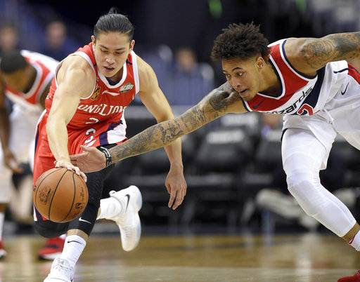Washington Wizards forward Kelly Oubre Jr., right, reaches for the ball next to Guangzhou Long-Lions' Chen Yingjun during the first half of NBA basketball exhibition game, Monday, Oct. 2, 2017, in Washington.