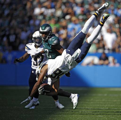 Los Angeles Chargers wide receiver Tyrell Williams, above, leaps over Philadelphia Eagles outside linebacker Mychal Kendricks, below right, during the second half of an NFL football game Sunday, Oct. 1, 2017, in Carson, Calif.