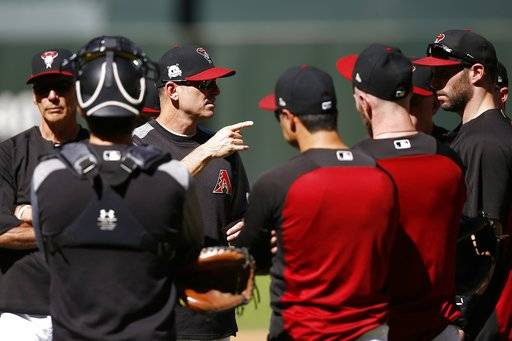 Arizona Diamondbacks manager Torey Lovullo, third from left, talks with his players during practice at Chase Field as the team gets ready for a National League wild-card playoff baseball game Monday, Oct. 2, 2017, in Phoenix. The Diamondbacks face the Colorado Rockies on Wednesday.