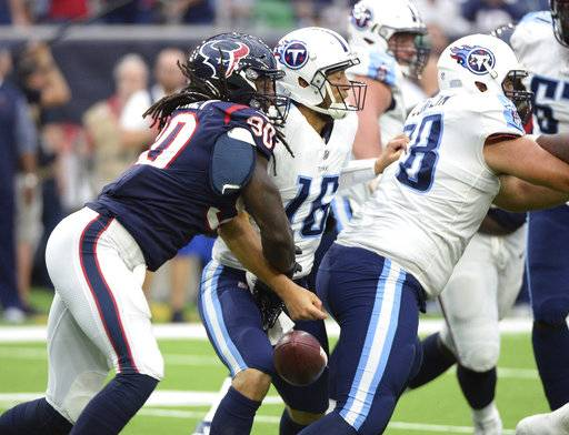 Houston Texans outside linebacker Jadeveon Clowney (90) steps the ball from Tennessee Titans quarterback Matt Cassel (16) during gate second half of an NFL football game Sunday, Oct. 1, 2017, in Houston. Houston recovered the ball.