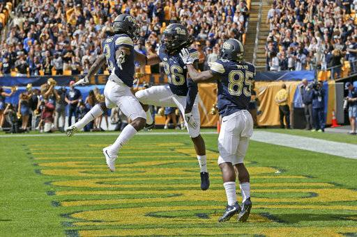Pittsburgh running back Chawntez Moss (26) celebrates with teammates Jester Weah (85) and Maurice Ffrench (2) after scoring a touchdown against Rice in the first quarter of an NCAA college football game, Saturday, Sept. 30, 2017, in Pittsburgh.