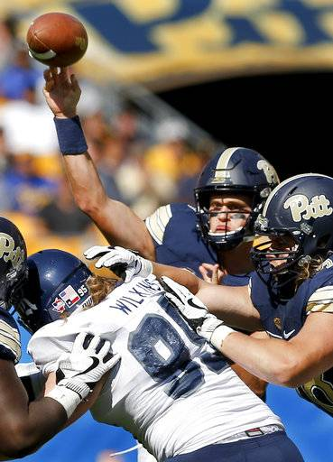 Pittsburgh quarterback Max Browne, top, passes as Rice defensive tackle Roe Wilkins (95) rushes during the second half of an NCAA college football game, Saturday, Sept. 30, 2017, in Pittsburgh. Pittsburgh won 42-10.
