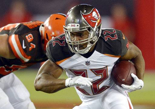 FILE - In this Aug. 26, 2017, file photo, Tampa Bay Buccaneers running back Doug Martin (22) eludes Cleveland Browns defensive end Carl Nassib (94) during the second quarter of an NFL preseason football game in Tampa, Fla. Martin is back from a four-game suspension for violating the NFL's policy on performance enhancers. The question is how soon will he be ready to contribute to an offense that can use his help.