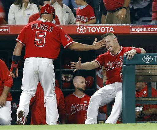 Los Angeles Angels' Albert Pujols (5) gets congratulations from Mike Trout after scoring on a single by C.J. Cron during the eighth inning of a baseball game against the Seattle Mariners in Anaheim, Calif., Friday, Sept. 29, 2017.