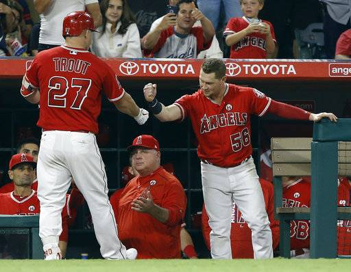 Los Angeles Angels' Mike Trout (27) gets congratulations from Kole Calhoun, right, and manager Mike Scioscia, center below, after hitting a home run, his second of the night, during the eighth inning of a baseball game against the Seattle Mariners in Anaheim, Calif., Friday, Sept. 29, 2017. The Angels won 6-5.