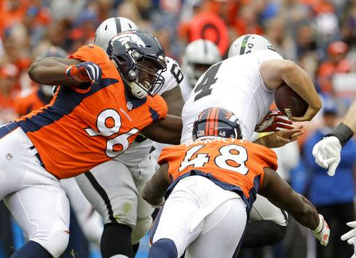 Oakland Raiders quarterback Derek Carr (4) is tackled by Denver Broncos defensive end Shelby Harris, left, and outside linebacker Shaquil Barrett during the second half of an NFL football game Sunday, Oct. 1, 2017, in Denver. Carr was juried on the play.