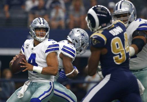 Dallas Cowboys quarterback Dak Prescott (4) prepares to throw a pass under pressure form Los Angeles Rams linebacker Robert Quinn (94) in the first half of an NFL football game, Sunday, Oct. 1, 2017, in Arlington, Texas.