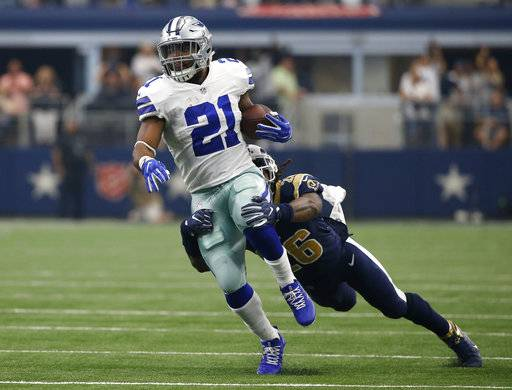 Dallas Cowboys running back Ezekiel Elliott (21) attempts to break the tackle by Los Angeles Rams linebacker Mark Barron after Elliott gained long yardage after catching a pass in the first half of an NFL football game, Sunday, Oct. 1, 2017, in Arlington, Texas.
