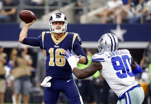 Los Angeles Rams quarterback Jared Goff (16) throws a pass under pressure from Dallas Cowboys defensive end DeMarcus Lawrence (90) in the first half of an NFL football game, Sunday, Oct. 1, 2017, in Arlington, Texas.