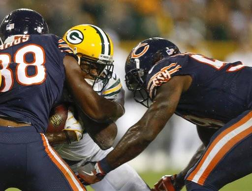 FILE - In this Thursday, Sept. 28, 2017, file photo, Green Bay Packers' Davante Adams is hit by Chicago Bears' Adrian Amos and Danny Trevathan during the second half of an NFL football game, in Green Bay, Wis. Adams was lucky he wasn't more seriously injured on Trevathan's illegal hit on the Green Bay receiver. And Chicago's thumping linebacker, who was flagged and suspended for two games, is fortunate he wasn't ejected.