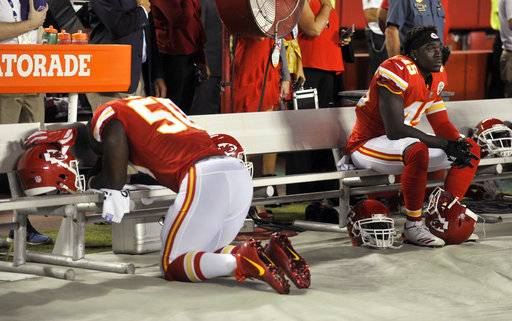 Kansas City Chiefs linebacker Justin Houston (50) kneels and linebacker Ukeme Eligwe (45) sits on the bench during the national anthem before the team's NFL football game against the Washington Redskins in Kansas City, Mo., Monday, Oct. 2, 2017.
