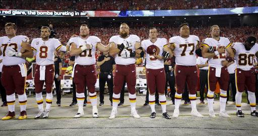 Washington Redskins link arms during the national anthem before an NFL football game against the Kansas City Chiefs in Kansas City, Mo., Monday, Oct. 2, 2017.