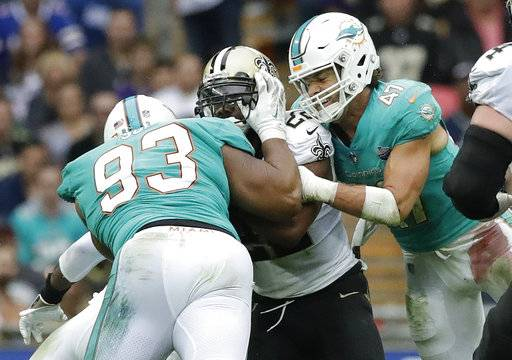 Miami Dolphins defensive tackle Ndamukong Suh (93) gets his hands inside the face mask of New Orleans Saints running back Mark Ingram, center, as middle linebacker Kiko Alonso (47) converges on the play during the second half of an NFL football game at Wembley Stadium in London, Sunday Oct. 1, 2017.