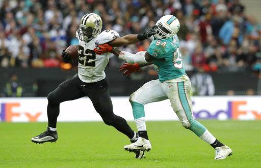 New Orleans Saints running back Mark Ingram (22) stiff arms Miami Dolphins linebacker Lawrence Timmons (94) during the second half of an NFL football game at Wembley Stadium in London, Sunday Oct. 1, 2017.