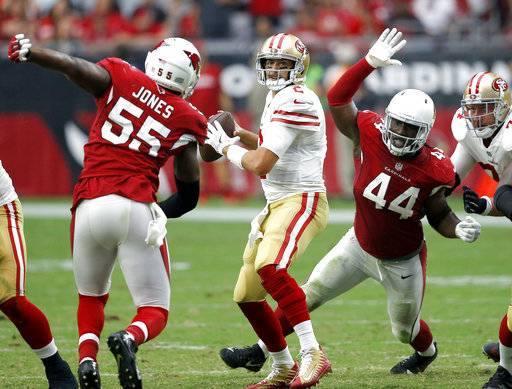 San Francisco 49ers quarterback Brian Hoyer looks to throw as Arizona Cardinals outside linebacker Markus Golden (44) and outside linebacker Chandler Jones (55) pursue during the second half of an NFL football game, Sunday, Oct. 1, 2017, in Glendale, Ariz.