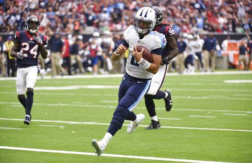 Tennessee Titans quarterback Marcus Mariota (8) scores against the Houston Texans during the first half of an NFL football game, Sunday, Oct. 1, 2017, in Houston.