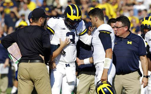 FILE - In this Saturday, Sept. 23, 2017, file photo, Michigan quarterback Wilton Speight (3) is helped off the field after getting injured in the first half of an NCAA college football game against Purdue in West Lafayette, Ind. Seventh-ranked Michigan has lost quarterback Wilton Speight for multiple weeks with an undisclosed injury. Coach Jim Harbaugh said Monday, Oct. 2, 2017, that John O'Korn will start Saturday night when the Wolverines play against Michigan State.