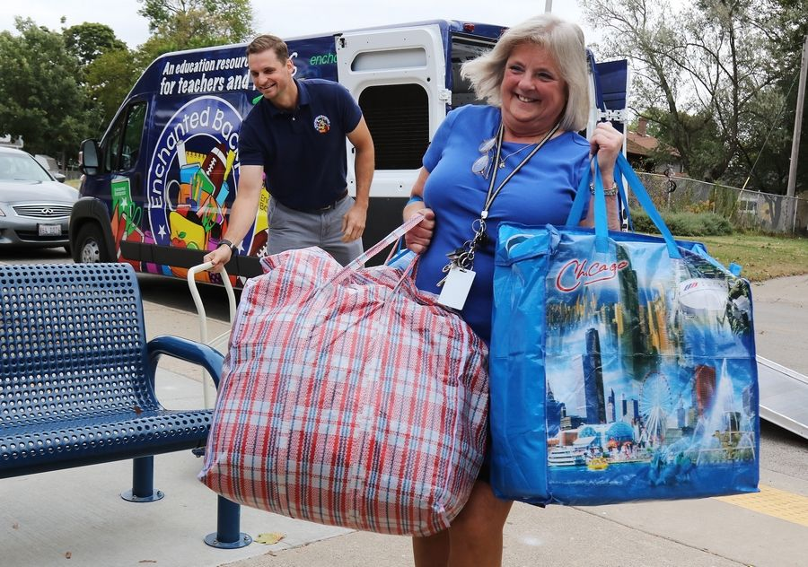 Wauconda Grade School Principal Debbie Monroe unloads bags of clothing Tuesday as the nonprofit group Enchanted Backpack delivered classroom supplies to the school Tuesday. More than 250 boxes of pencils, notebooks, books, games and more were delivered by the charity organization.