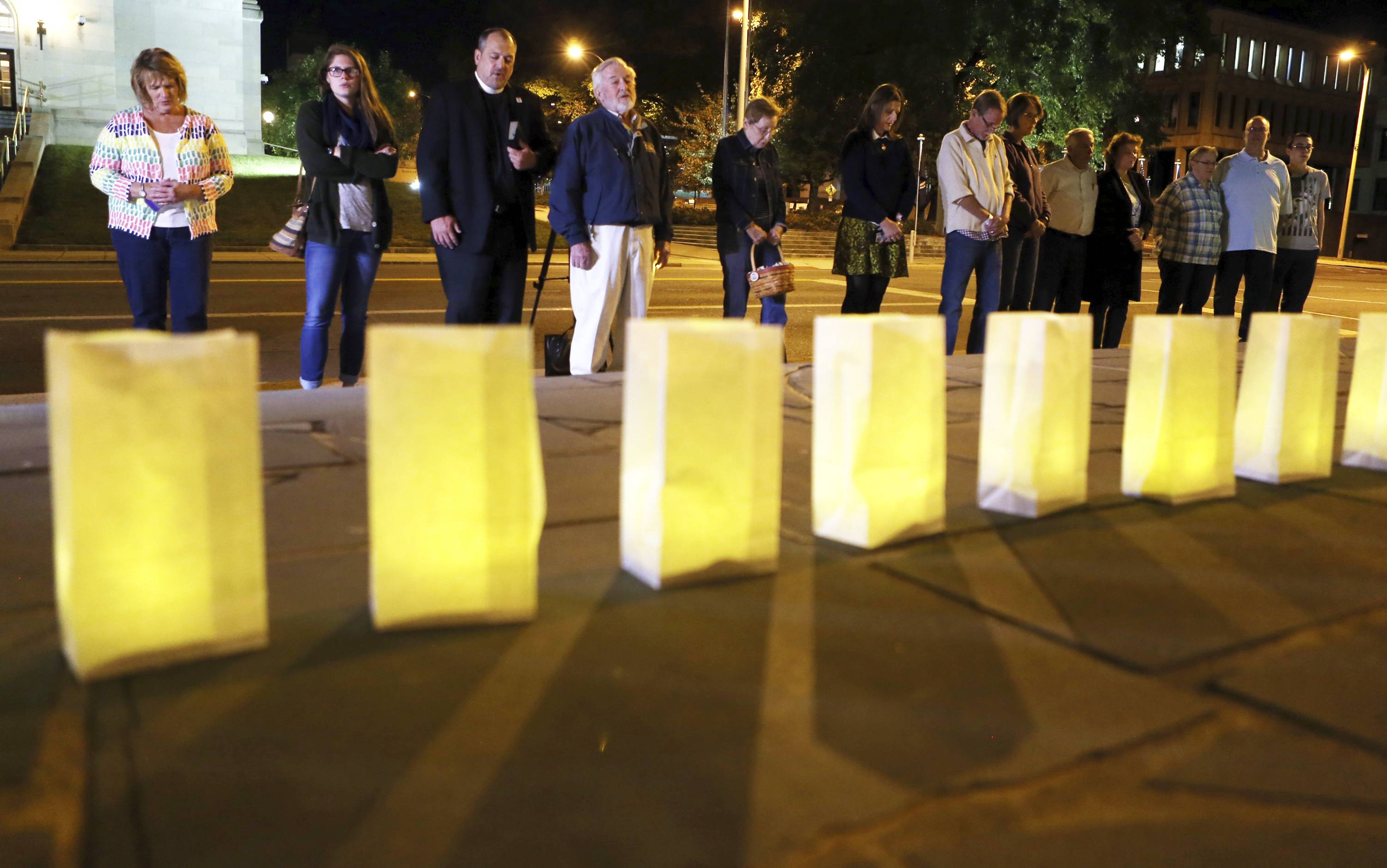 Luminaries for victims of the Sunday evening shooting tragedy in Las Vegas are lit on the front steps of Greene Memorial United Methodist Church surrounded by those brought together in prayer and solidarity on Monday, Oct. 2, 2017, in Roanoke, Va. (Heather Rousseau/The Roanoke Times via AP)