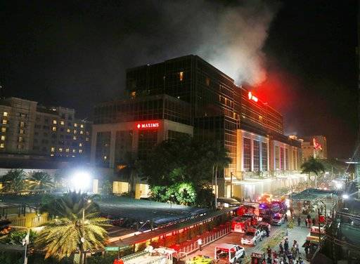 FILE - In this Friday, June 2, 2017, file photo, smoke rises from an attack inside the Resorts World Manila complex in suburban Pasay city, southeast of Manila, Philippines. Across the globe, risks of terrorism and other violence have made tight security at hotels and resorts routine. The most recent major attack in Asia, at the Resorts World Manila casino in the Philippines, shares similarities with the shooting Sunday night in Las Vegas that killed 59 and injured more than 500 people.