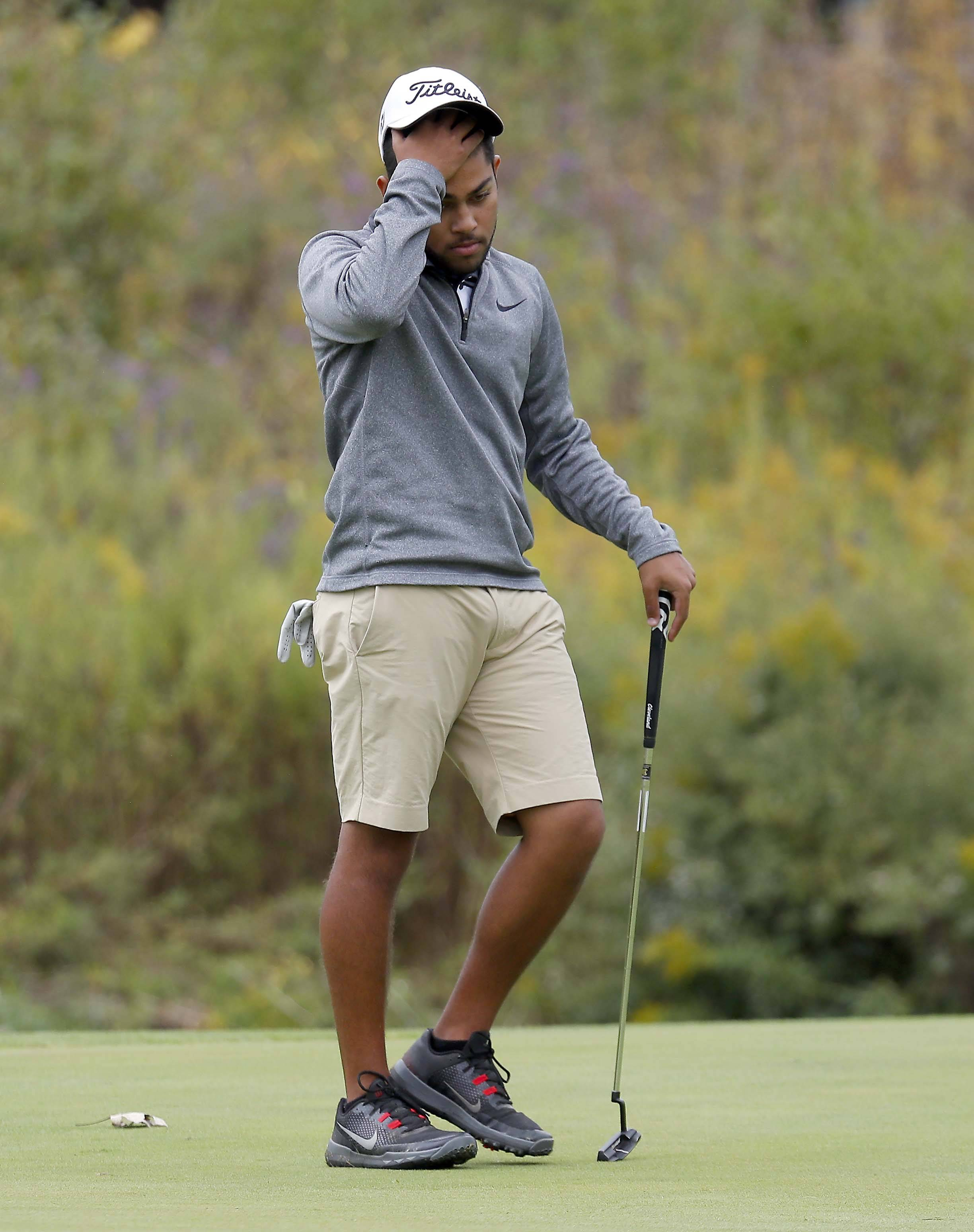 South Elgin's Nathan Mehta reacts to his putt on the 8th green Tuesday during the Geneva boys golf regional at Mill Creek Golf Club.