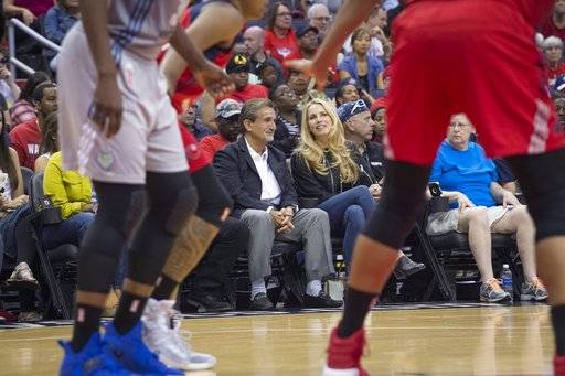 In this image taken Sept. 17, 20, 2017, and provided by Monumental Sports & Entertainment, Ted Leonsis, left, chairman and CEO of Monumental Sports & Entertainment, sits with billionaire executive Laurene Powell Jobs during a basketball game in Washington, D.C. Powell Jobs has agreed to buy a 20 percent stake in Ted Leonsis' Monumental Sports & Entertainment., pending approval from the NBA and NHL. Monumental owns the Washington Wizards, Capitals, Mystics and the Arena Football League's Washington Valor and Baltimore Brigade. (Barbara Kinney/Monumental Sports & Entertainment via AP)