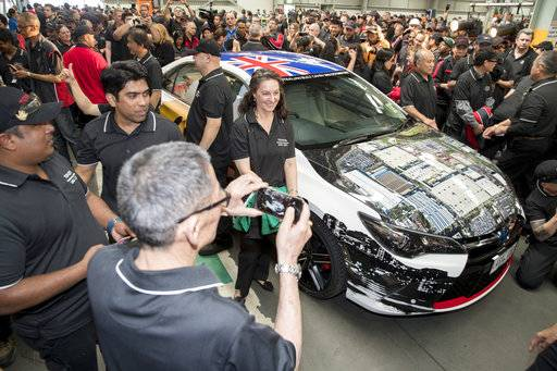 In this photo provided by Toyota Australia, employees gather around the last Toyota car produced in Australia as it leaves the production line in Melbourne, Tuesday, Oct. 3, 2017. Toyota closed its manufacturing plant in Melbourne, ending 54 years of production by the Japanese firm in Australia, the first country outside of Japan where the company made cars. (Toyota Australia via AP)