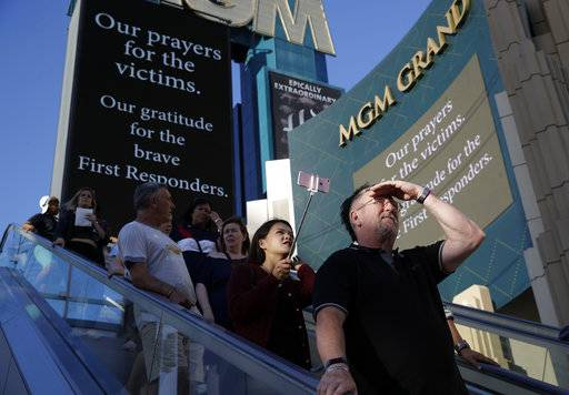 People take an outdoor escalator past a sign asking for prayers for the victims outside of the MGM hotel in Las Vegas, Tuesday, Oct. 3, 2017. A gunman opened fire on an outdoor music concert on Sunday. It was the deadliest mass shooting in modern U.S. history, with dozens of people killed and hundreds injured, some by gunfire, some during the chaotic escape.