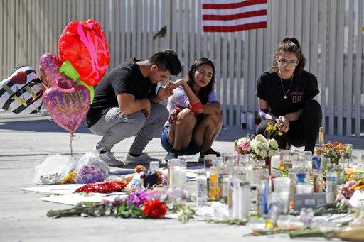 Roberto Lopez, from left, Briana Calderon and Cynthia Olvera, of Las Vegas, pause at a memorial site on Tuesday, Oct. 3, 2017 in Las Vegas. Investigators trying to figure out why Stephen Paddock gunned down dozens of people from his high-rise hotel suite are analyzing his computer and cellphone, looking at casino surveillance footage and seeking to interview his longtime girlfriend.