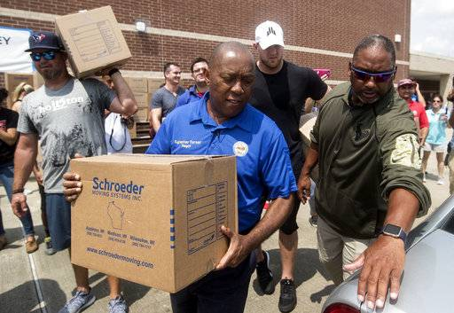 FILE - In this Sept. 3, 2017 file photo, Houston Mayor Sylvester Turner, center, with Houston Texans Shane Lechler, left, and J.J. Watt, second right, distribute relief supplies to people impacted by Hurricane Harvey in Houston. The Harvey relief fund established by Houston's top elected leaders has issued its first grants, giving out $7.5 million with an emphasis on getting people still displaced by the storm into temporary housing. Turner, and other leaders of the fund announced the grants Tuesday, Oct. 3. (Brett Coomer/Houston Chronicle via AP, Pool)