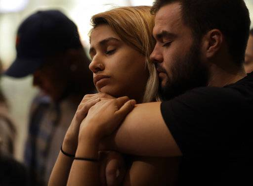 University of Nevada Las Vegas students Raymond Lloyd, right, and Karla Rodriguez take part in a vigil Monday, Oct. 2, 2017, in Las Vegas. A gunman on the 32nd floor of the Mandalay Bay casino hotel rained automatic weapons fire down on the crowd of over 22,000 at an outdoor country music festival Sunday.