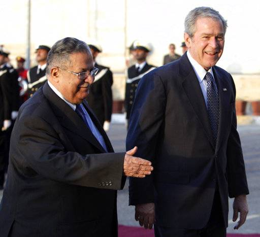 FILE - In this Dec. 14, 2008 file photo, then U.S. President George W. Bush, right, walks with Iraqi President Jalal Talabani in Baghdad, Iraq. Talabani, a lifelong fighter for Iraq's Kurds who rose to become the country's president, presenting himself as a unifying father figure to temper the potentially explosive hatreds among Kurds, Shiites and Sunnis has died in a Berlin hospital at the age of 83.