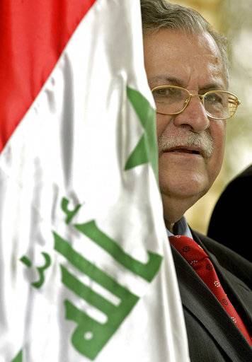 FILE - In this July 23, 2005, file photo, Iraqi President Jalal Talabani peers from behind the Iraqi flag during a press briefing with US Ambassador to Iraq Zalmay Khalilzadat Talabani's residence in Baghdad, Iraq. Talabani, a lifelong fighter for Iraq's Kurds who rose to become the country's president, presenting himself as a unifying father figure to temper the potentially explosive hatreds among Kurds, Shiites and Sunnis has died in a Berlin hospital at the age of 83.
