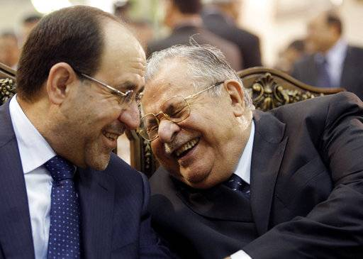 FILE - In this June. 27, 2009 file photo, Iraq's Prime Minister Nouri al-Maliki, left, and President Jalal Talabani, right, react, at a ceremony marking the death of Mohammed Baqir al-Hakim in Baghdad, Iraq. Talabani, a lifelong fighter for Iraq's Kurds who rose to become the country's president, presenting himself as a unifying father figure to temper the potentially explosive hatreds among Kurds, Shiites and Sunnis has died in a Berlin hospital at the age of 83.