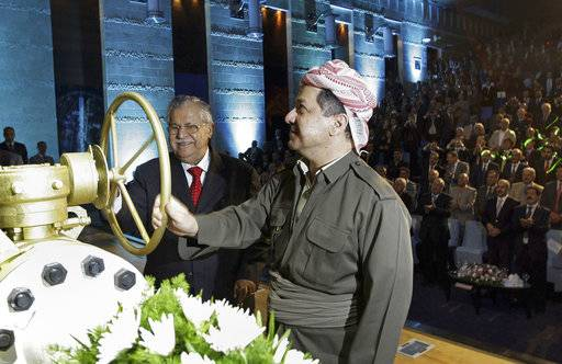 FILE - In this June 1, 2009 file photo, then Kurdish president Massud Barzani, right, and then Iraqi President Jalal Talabani open a ceremonial valve during an event to celebrate the start of oil exports from the autonomous region of Kurdistan, in the northern Kurdish city of Irbil, Iraq. Talabani, a lifelong fighter for Iraq's Kurds who rose to become the country's president, presenting himself as a unifying father figure to temper the potentially explosive hatreds among Kurds, Shiites and Sunnis has died in a Berlin hospital at the age of 83.