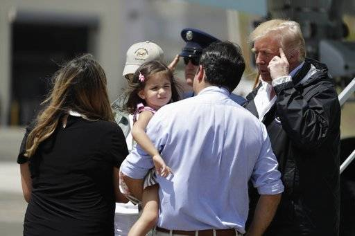 President Donald Trump talks with Governor Ricardo Rosselló, center, carrying his daughter in his arms after his arrival at the Luis Muñiz Air National Guard Base in San Juan, Puerto Rico, Tuesday, Oct. 3, 2017. Trump is visiting Puerto Rico in the wake of Hurricane Maria.