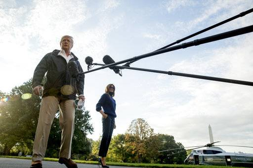 President Donald Trump, accompanied by first lady Melania Trump, listens to questions from reporters as he walks to board Marine One on the South Lawn of the White House in Washington, Tuesday, Oct. 3, 2017, for a short trip to Andrews Air Force Base, Md. and then on to Puerto Rico.
