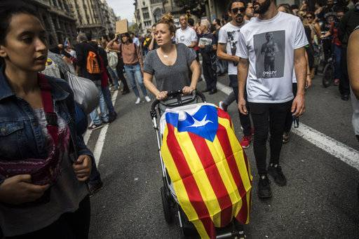 A woman pushes a baby's stroller covered with a ''estelada'' or Catalonia independence flag during a one-day strike in Barcelona, Spain, Tuesday Oct. 3, 2017. Labor unions and grassroots pro-independence groups are urging workers to hold partial or full-day strikes throughout Catalonia to protest alleged brutality by police during a referendum on the region's secession from Spain that left hundreds of people injured.