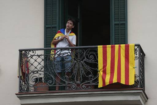 A youth stands on a balcony with a ''estelada'' or Catalonia independence flag over his shoulders while protesters below demonstrate outside the National police headquarters during a one-day strike in Barcelona, Spain, Tuesday Oct. 3, 2017. Labor unions and grassroots pro-independence groups are urging workers to hold partial or full-day strikes throughout Catalonia to protest alleged brutality by police during a referendum on the region's secession from Spain that left hundreds of people injured.