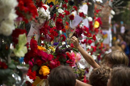 Catalan boys place flowers at the main gate of Ramon Llull school condemning the National Police attempt to try to stop the voting during the referendum in Barcelona, Spain, Tuesday Oct. 3, 2017. Labor unions and grassroots pro-independence groups are urging workers to hold partial or full-day strikes throughout Catalonia to protest alleged brutality by police during a referendum on the region's secession from Spain that left hundreds of people injured.