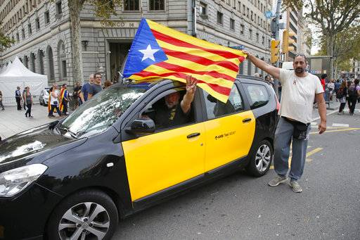 A taxi driver with a ''estelada'' or Catalonia independence flag fixed to his car, gestures as a protester helps to extend the flag during protest near the national police headquarters during a one-day strike in Barcelona, Spain, Tuesday Oct. 3, 2017. Labor unions and grassroots pro-independence groups are urging workers to hold partial or full-day strikes throughout Catalonia to protest alleged brutality by police during a referendum on the region's secession from Spain that left hundreds of people injured.