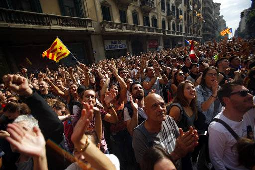 Demonstrators gather in protest in front of Spanish police station in downtown Barcelona, Spain, Tuesday Oct. 3, 2017. Labor unions and grassroots pro-independence groups are urging workers to hold partial or full-day strikes and demonstrations throughout Catalonia to protest alleged brutality by police during a referendum on the region's secession from Spain that left hundreds of people injured.