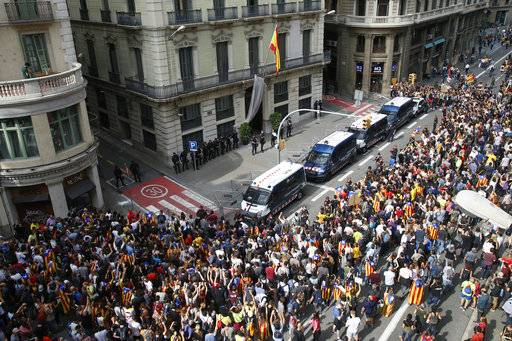 Catalan regional mossos d'esquadra police vans form a protective barrier between protesters and the national police headquarters during a one-day strike in Barcelona, Spain, Tuesday Oct. 3, 2017. Labor unions and grassroots pro-independence groups are urging workers to hold partial or full-day strikes throughout Catalonia to protest alleged brutality by police during a referendum on the region's secession from Spain that left hundreds of people injured.