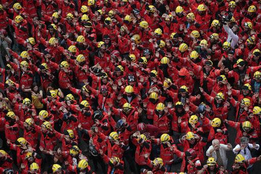 Firefighters join protesters outside the Spanish government delegation during a one-day strike in Barcelona, Spain, Tuesday Oct. 3, 2017. Labor unions and grassroots pro-independence groups are urging workers to hold partial or full-day strikes throughout Catalonia to protest alleged brutality by police during a referendum on the region's secession from Spain that left hundreds of people injured.
