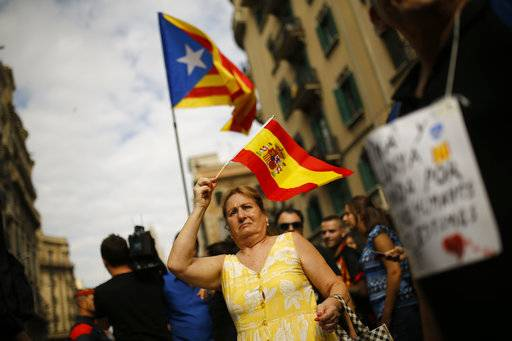 A woman holds a Spanish flag to support Spanish police as pro-independence protesters gather in front of the national police headquarters in Barcelona, Spain, Tuesday Oct. 3, 2017. Labor unions and grassroots pro-independence groups are urging workers to hold partial or full-day strikes throughout Catalonia to protest alleged brutality by police during a referendum on the region's secession from Spain that left hundreds of people injured.