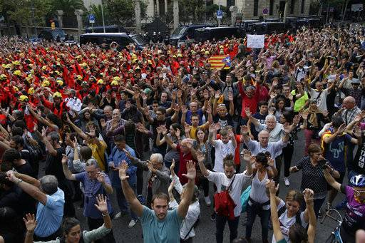Protesters raise their arms outside the Spanish government delegation during a one-day strike in Barcelona, Spain, Tuesday Oct. 3, 2017. Labor unions and grassroots pro-independence groups are urging workers to hold partial or full-day strikes throughout Catalonia to protest alleged brutality by police during a referendum on the region's secession from Spain that left hundreds of people injured.