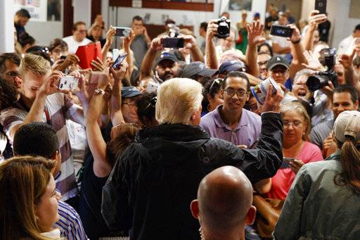 President Donald Trump hands out canned goods and other supplies at Calvary Chapel, Tuesday, Oct. 3, 2017, in Guaynabo, Puerto Rico. Trump is in Puerto Rico to survey hurricane damage.