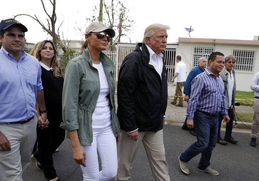 President Donald Trump and first lady Melania Trump take a walking tour with Puerto Rico Governor Ricardo Rosselló, left, and his wife Beatriz Areizaga, to survey hurricane damage and recovery efforts in a neighborhood in Guaynabo, Puerto Rico, Tuesday, Oct. 3, 2017.