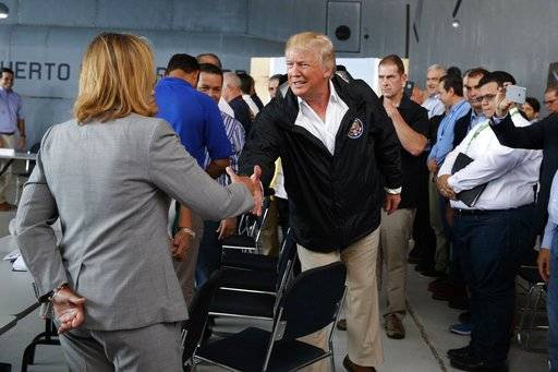 President Donald Trump shakes hands with San Juan Mayor Carmen Yulin Cruz during a briefing on hurricane recovery efforts with first responders at Luis Muniz Air National Guard Base, Tuesday, Oct. 3, 2017, in San Juan, Puerto Rico.